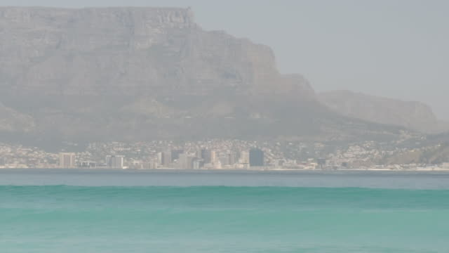 exterior shots of waves rolling into a beach with the skyline of cape town on 24 september 2019 in cape town, south africa - テーブルマウンテン国立公園点の映像素材/bロール