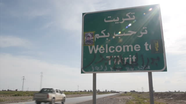 exterior shots of welcome to tikrit road sign and on the reverse goodbye tikrit on march 17 2015 in saladin governorate iraq - home guard britannica video stock e b–roll