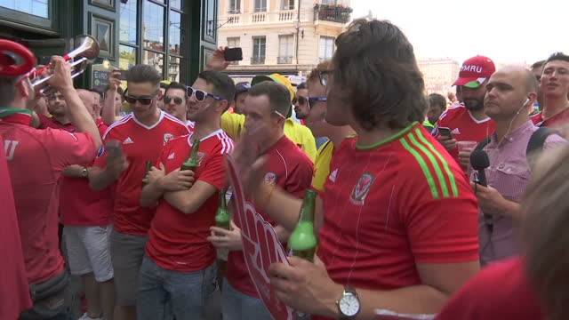 vídeos de stock, filmes e b-roll de exterior shots of welsh football fans playing in a band as other fans sing in celebration in the countdown to the side's semi final match with... - olympique lyonnais