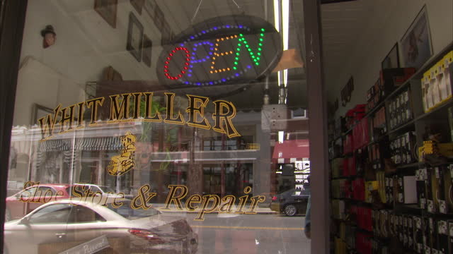 exterior shots of whit miller's shoe store with a framed photo of john wayne and a 'he is risen' cross inside the doorway on april 20th 2016 in... - ノースカロライナ州点の映像素材/bロール