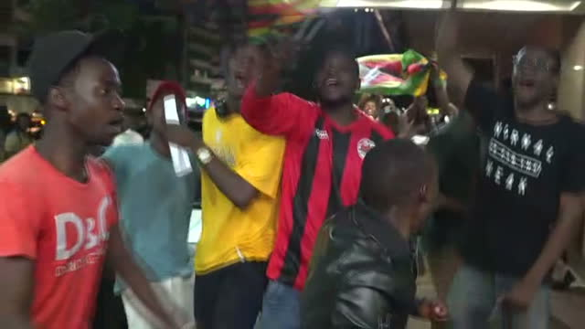 Exterior shots of wildly cheering jubilant people celebrating in the streets of Harare after the resignation of Robert Mugabe on 21 November 2017 in...