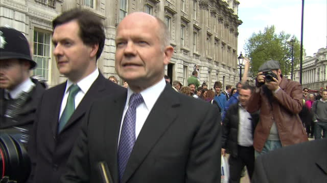 vídeos de stock, filmes e b-roll de exterior shots of william hague george osborne and oliver letwin walking towards camera after a meeting with the liberal democrats in the wake of the... - 2010