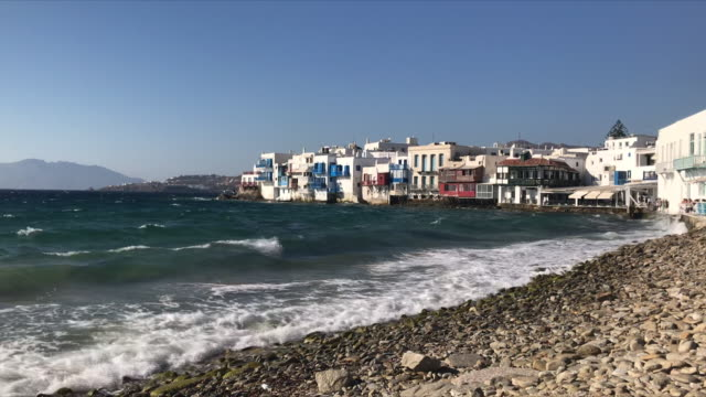 exterior shots of windmills on mykonos and waves rolling in to beach and buildings in the old town area on 22 august 2020 in mykonos greece - mykonos stock videos & royalty-free footage