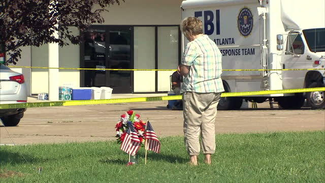 Exterior shots of woman laying floral tribute and flags at seen of shooting after Muhammad Youssef Abdulazeez opened fire at an Army recruitment...