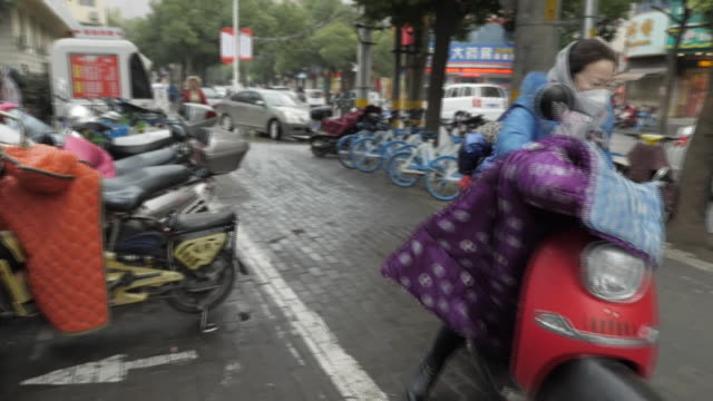 exterior shots of woman on motorcycle with a child both wearing masks and ambulances parked outside hospital on 24 january 2020 in wuhan china - wuhan stock-videos und b-roll-filmmaterial