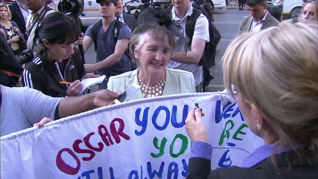 exterior shots of woman supporting oscar pistorius with sign oscar you were you are will always be inspiration a hero and grab about how oscar... - ピストリウス恋人射殺事件点の映像素材/bロール