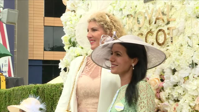 exterior shots of women posing for photo op in front of royal ascot sign wearing formal summer dresses and facinators at ascot racecourse on june 20,... - イギリス アスコット競馬場点の映像素材/bロール