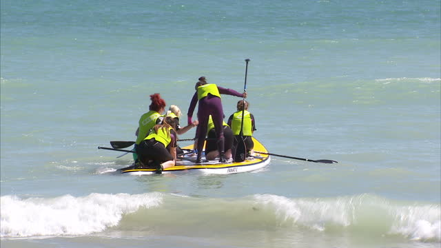 exterior shots of women using a stand up paddle board at sea on 10 july 2015 in worthing, united kingdom - worthing点の映像素材/bロール