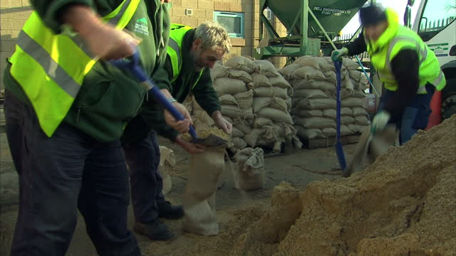 exterior shots of workers filling sandbags at a depot near shepperton, and a 4x4 vehicle driving along a flooded road. flood levels continue to rise... - 緊急用具点の映像素材/bロール