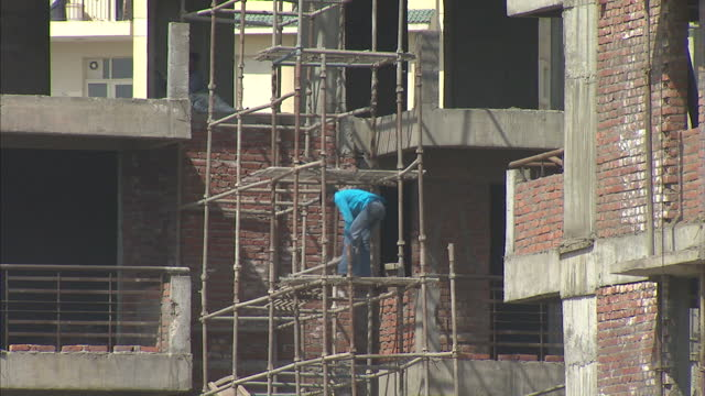 exterior shots of workers on large construction site. exterior shots of bricks being laid and materials passed up on pully. delhi gvs on march 10,... - 50 seconds or greater stock videos & royalty-free footage