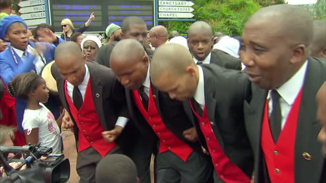 Exterior shots of worshippers singing dancing outside Bryanston Methodist Church on a National day of prayers for Nelson Mandela following his death...