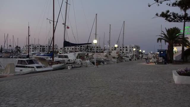 vidéos et rushes de exterior shots of yachts in a harbour and surrounding convenience and tourist shops on july 9 2015 in sousse tunisia - entourer