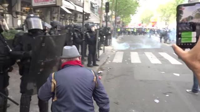 vídeos de stock, filmes e b-roll de exterior shots of yellow vest protesters cgt union banners and police with riot shields as tear gas rounds are fired in the streets of paris during... - 1 de maio