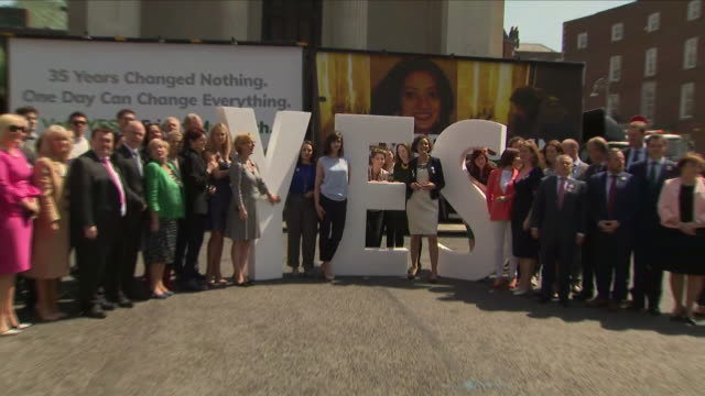 exterior shots of 'yes' abortion campaigners stood and pose for press photos and stood next to a large 'yes' sign on 23rd may 2018 in dublin ireland - abortion stock videos and b-roll footage