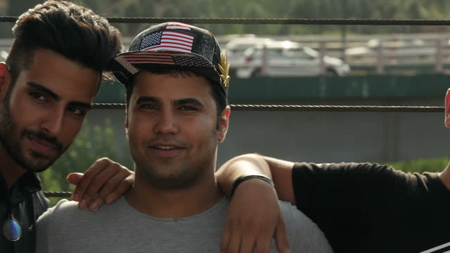 Exterior shots of young Iranians smiling one with a baseball cap with a Stars and Stripes on July 29 2016 in Tehran Iran