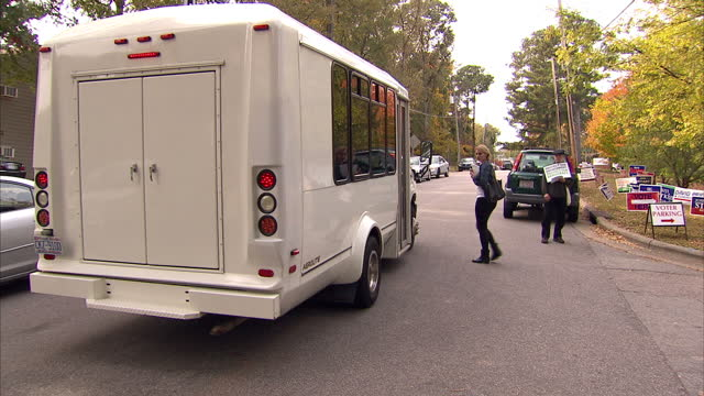 vídeos de stock e filmes b-roll de exterior shots of young voters disembarking buses on arrival at a polling station in raleigh north carolina and being given various political... - partido democrático eua