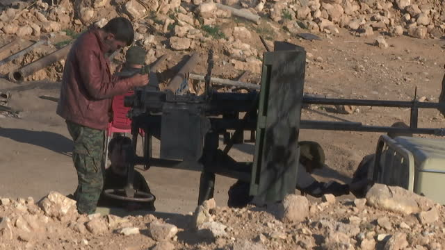 exterior shots of ypg fighters near ayn issa,including two men servicing the gun on the back of an improvised fighting vehicle.>> on december 15,... - クルド人点の映像素材/bロール