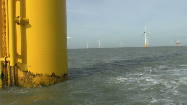 Exterior shots off shore wind farm with wind turbines tug boat pushing one of the large turbines Exterior shots offshore wind farm The world's...