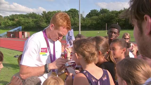 stockvideo's en b-roll-footage met exterior shots olympic gold medalist greg rutherford, long jumper, signing autographs for fans - signeren