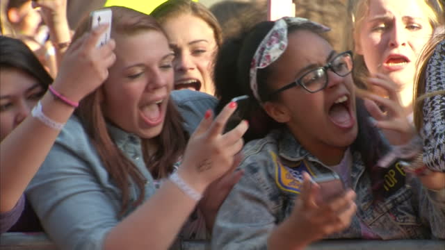 exterior shots one direction fans in leicester square screaming for the band directioners cheering. one direction fans cheering taking pictures on... - boy band stock videos & royalty-free footage