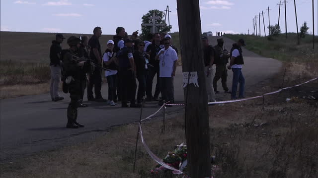 exterior shots osce workers inspecting mh17 crash site from behind cordon tape with pro russian separatists stood guard. - ロシア軍点の映像素材/bロール