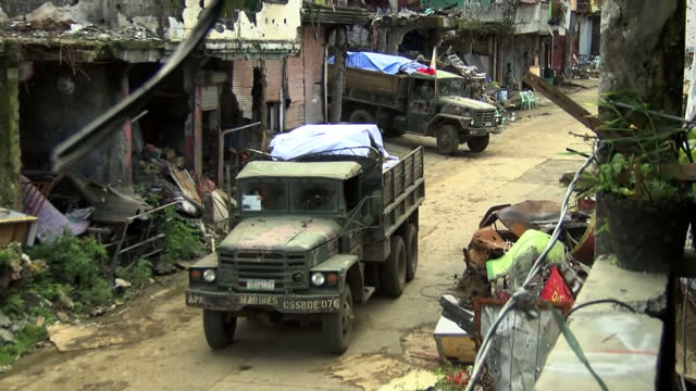 exterior shots over a street of badly damaged buildings as filipino army trucks potentially carrying bodies after the liberation of marawi from isis... - terrorism stock videos & royalty-free footage