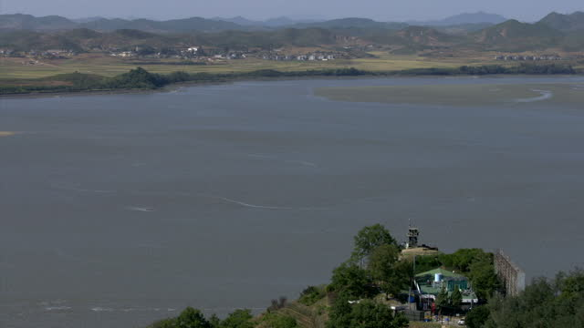 exterior shots over the demilitarized zone between north and south korea from a south korean high point looking over north korean structures and... - 2013年 北朝鮮の核実験点の映像素材/bロール