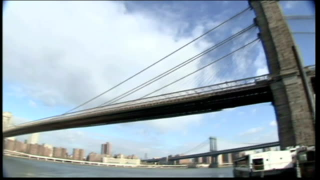 exterior shots over the east river panning along the brooklyn bridge to the lower manhattan skyline on february 06, 2008 in new york city. - brooklyn bridge stock videos & royalty-free footage