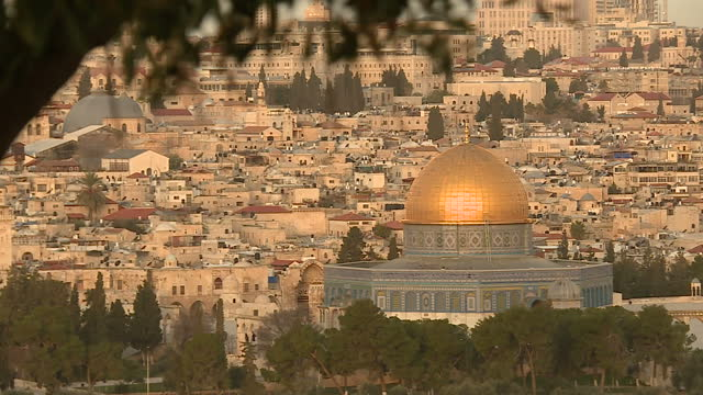 stockvideo's en b-roll-footage met exterior shots over the old city of jerusalem at sunrise from the mount of olives with the sun reflecting on the al aqsa mosque traffic passing the... - rotskoepel