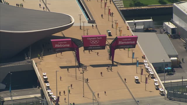 exterior shots over the olympic park showing the olympic stadium, aquatics centre, water polo complex & the olympic park entrance & signs sky news... - ゴールを狙う点の映像素材/bロール