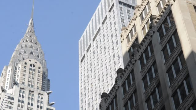 vídeos de stock e filmes b-roll de exterior shots pan up the side of the chrysler building and pause on the iconic needle of the landmark skyscraper in new york ny rack focus shot of... - prédio chrysler