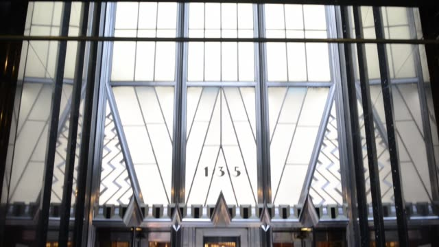 exterior shots pan up the side of the chrysler building and pause on the iconic needle of the landmark skyscraper in new york, ny, interior shots of... - chrysler building stock videos & royalty-free footage