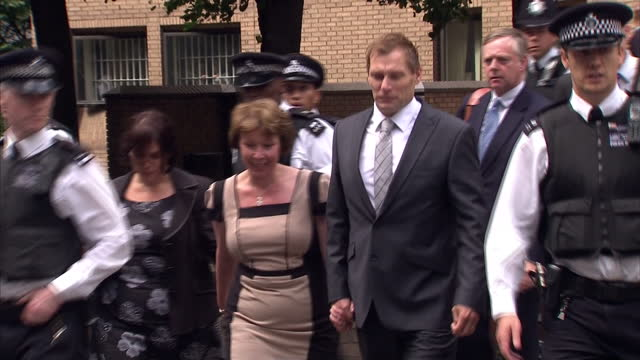 exterior shots pc simon harwood walks from southwark crown court escorted by police officers through press scrum to waiting vehicle a police officer... - サウスワーク刑事法院点の映像素材/bロール