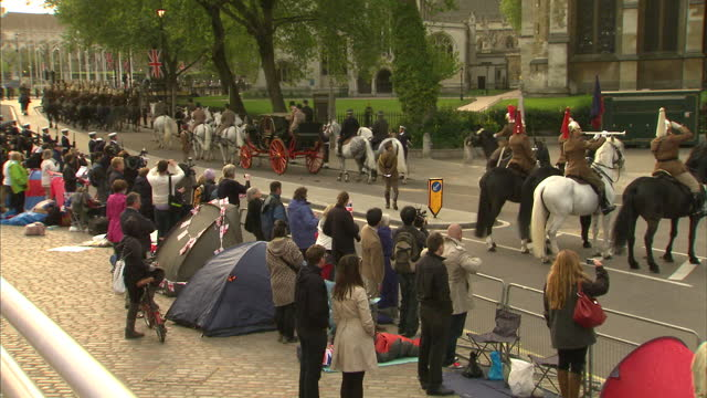 vídeos de stock e filmes b-roll de exterior shots people camped outside westminster abbey watch as the members of the household cavalry ride past escorting the queen's carriage... - exército britânico