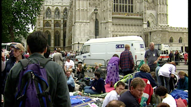 exterior shots people camping, waiting outside westminster abbey, reading newspapers, ok magazine on in london, england. - death stock videos & royalty-free footage