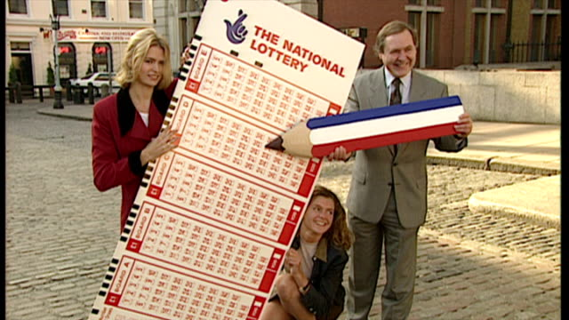 exterior shots, people pose in covent garden with a giant oversized national lottery card and giant pencil on november 14, 1994 in london, england. - lotterie stock-videos und b-roll-filmmaterial