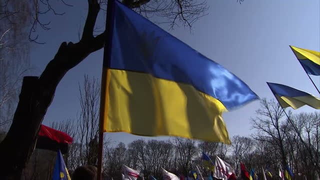 vídeos de stock e filmes b-roll de exterior shots people standing listening to speeches at patriotic rally, some holding ukrainian flags on march 09, 2014 in donetsk, ukraine. - ucrânia bandeira