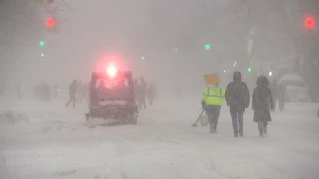 exterior shots people walking along road in thick snow as small nypd vehicle drives along road as winter storm jonas hits the us east coast on... - snow vehicle stock videos and b-roll footage