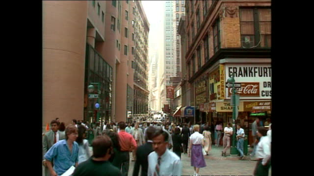 stockvideo's en b-roll-footage met exterior shots people walking along wall street with the nyse in the background and stock exchange workers sitting on steps on august 15 1990 in new... - wall street lower manhattan