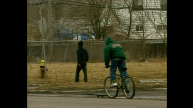 Exterior shots people walking past rundown buildings going about daily life in poverty stricken neighbourhood on March 12 1994 in Detroit Michigan