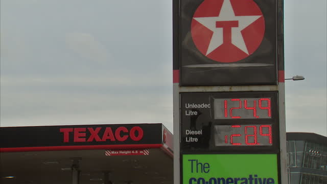 Exterior shots petrol prices at Shell petrol station wide shot vehicles leaving Shell petrol station man filling his car at petrol station pump...