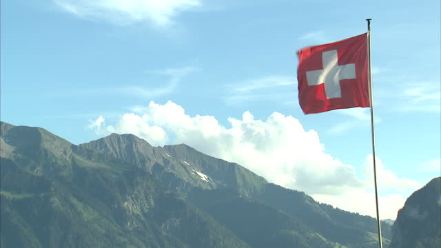 exterior shots picturesque thunersee lake with mountains in the background boats sailing on the lake and swiss flag blowing in wind on july 19 2016... - lake thun stock videos and b-roll footage