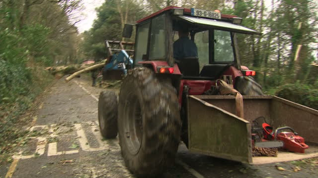 exterior shots police car driving around tree branches lying across country road and tractor removing cut branches during aftermath clear up of storm... - county cork stock videos & royalty-free footage