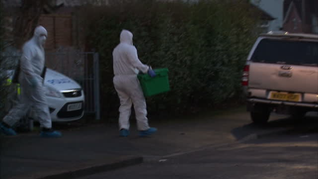 stockvideo's en b-roll-footage met exterior shots police cars parked in street near house in southmead exterior shots forensic officers removing evidence bags and boxes on march 02... - vermiste personen