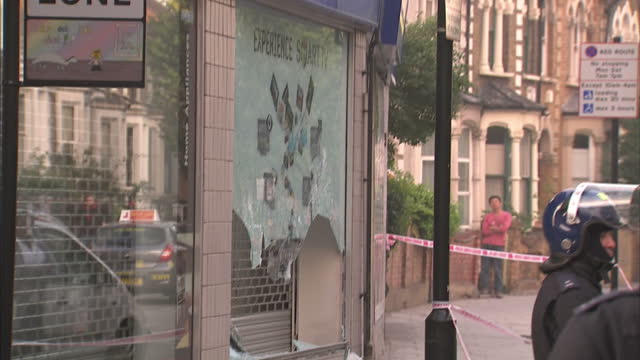 vidéos et rushes de exterior shots police guarding cordoned off area, damaged shops. exterior close up smashed in window & broken glass on pavement. general shot people... - hackney