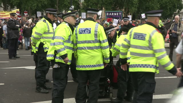 exterior shots police officers moving disabled antiausterity protester in wheelchair after he stopped in the middle of the road to block traffic... - george osborne stock videos & royalty-free footage