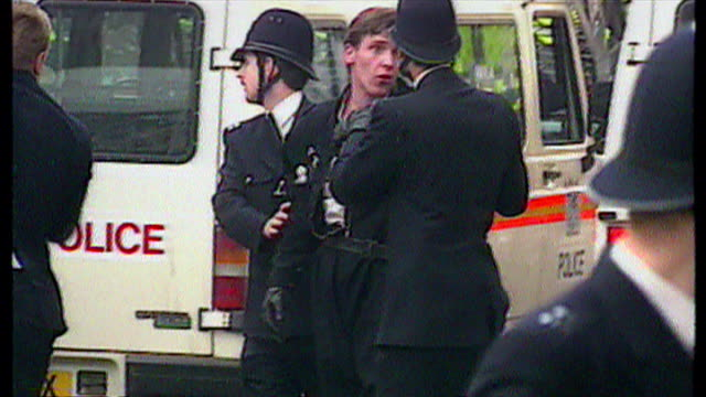 exterior shots police officers restraining antipoll tax protester in road and leading him away on march 31 1990 in london england - trattenere video stock e b–roll