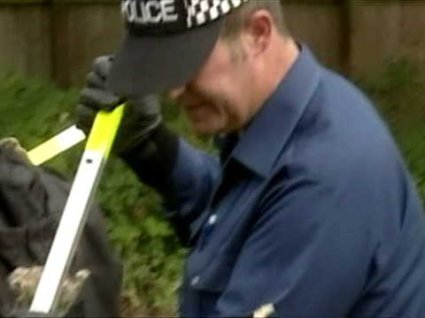 exterior shots police searching bushes and trees on roadside. police searching for holly & jessica on august 06, 2002 in cambridgeshire - searching点の映像素材/bロール