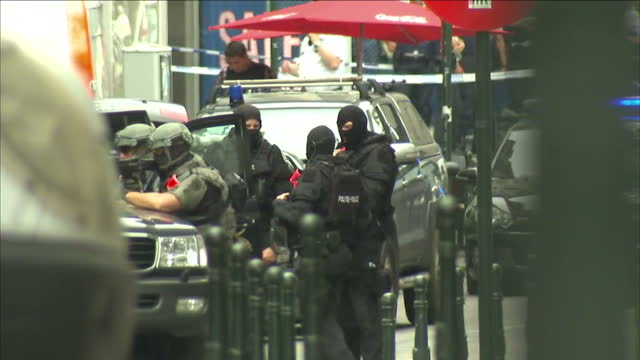 BRUSSELS Exterior shots police security in cordoned off street inc police in all black wearing masks body armour officer looking down sights of...