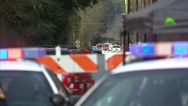 stockvideo's en b-roll-footage met exterior shots police state troopers at closed off road leading to scene of mudslide with lorry and emergency rescue vehicles heading to the scene on... - oso washington